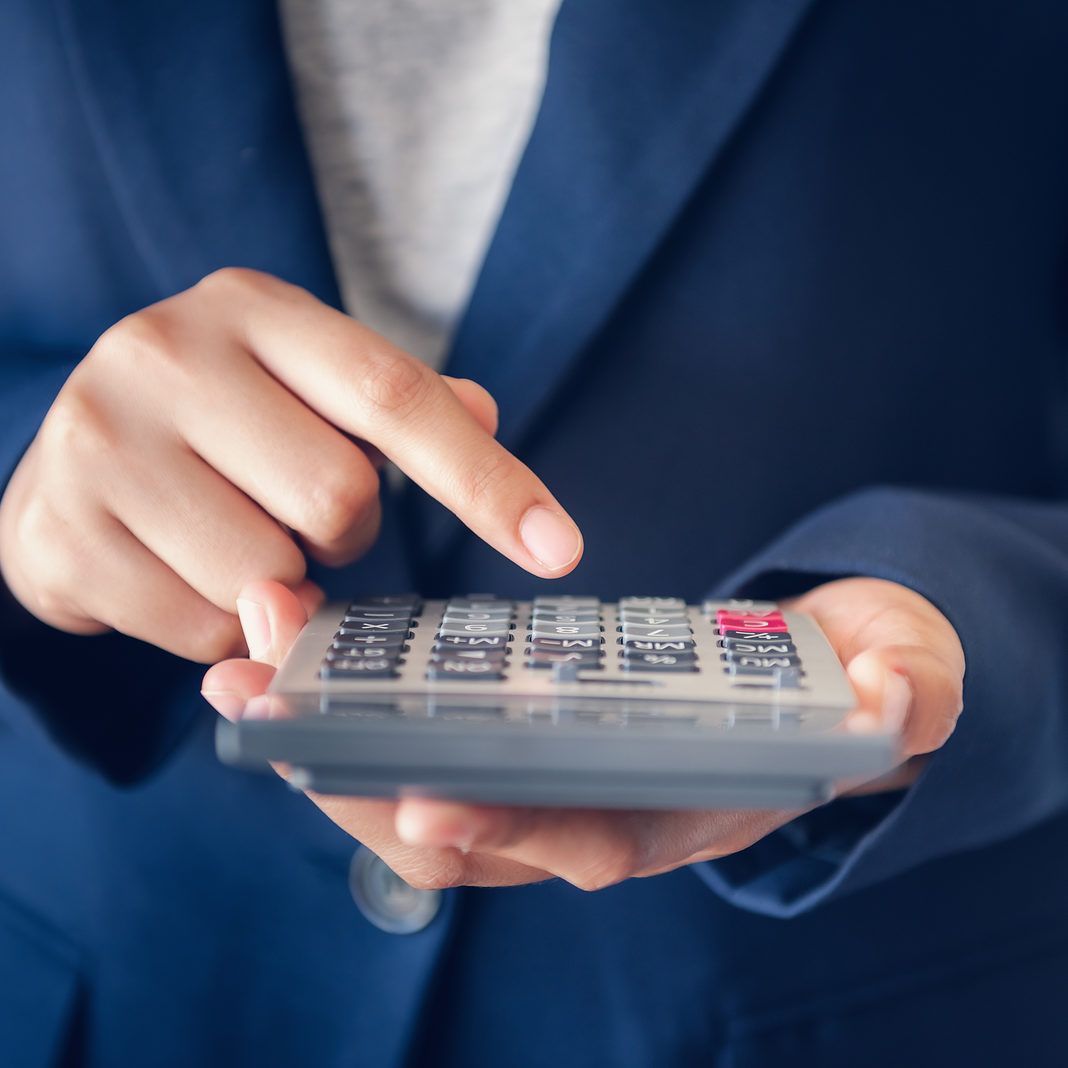 Close-Up of Business Accountant Financial Using Calculator for Estimated Tax Earning Account, Entrepreneurs Woman in Uniform Suit is Calculating Investment Income Tax. Business Finance and Investing.